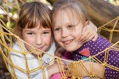 Happy little friends. Portrait of two adorable little girls in hammock Stock Photo