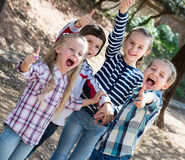 Happy little friends in city park. Group of excited cheerful little friends with thumbs up together in city park. Selective focus Royalty Free Stock Photography