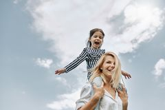 Happy little funny daughter on a piggy back ride with her happy mother on the sky background. Loving woman and her little girl stock images