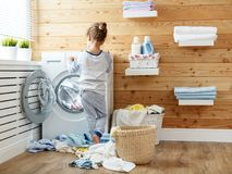 Happy  housewife child girl in laundry   with washing machine Royalty Free Stock Photography