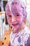 Happy little future artist covered in paint. Happy single little female future artist covered in various colors of paint at indoor art studio stock photography