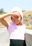 Happy Little Girl. A blue eyed blonde girl smiling and shading her eyes with her hand Royalty Free Stock Photography