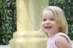 Happy little girl. Beside fountain Royalty Free Stock Photos