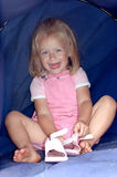 Happy little girl. A beautiful little caucasian white girl child in pink clothes and with happy laughing expression in her face putting on her shoes on the Royalty Free Stock Photography