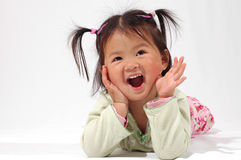 Happy Little Girl. Smiling little Asian girl, her mouth open and hands on her cheeks in surprise.  Laying on her stomach and leaning on her elbows, in a location Royalty Free Stock Photo
