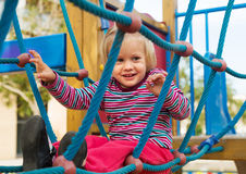 Happy little girl at action-oriented playground royalty free stock photo