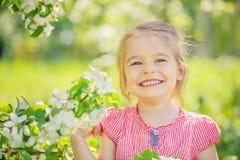 Happy little girl in apple tree garden Stock Photos