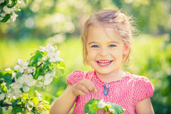 Happy little girl in apple tree garden Royalty Free Stock Photography