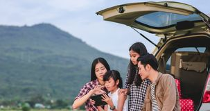 Happy little girl  with asian family sitting in the car for enjoying road trip and summer vacation in camper van royalty free stock photo