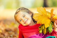 Happy little girl with autumn leaves. In the park Stock Images