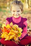 Happy little girl with autumn leaves Royalty Free Stock Image