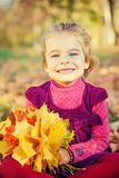 Happy little girl with autumn leaves Stock Images