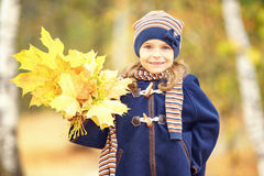 Happy little girl with autumn leaves. In the park Royalty Free Stock Photos