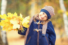 Happy little girl with autumn leaves Royalty Free Stock Images