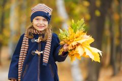 Happy little girl with autumn leaves. In the park Royalty Free Stock Image