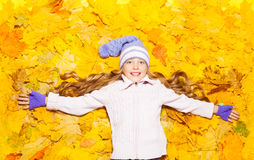 Happy little girl in autumn maple leaves Royalty Free Stock Photo