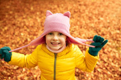Happy little girl in autumn park. Autumn, childhood, nature and people concept - happy little girl over fallen leaves in park Royalty Free Stock Images