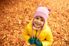 Happy little girl in autumn park. Autumn, childhood, nature and people concept - happy little girl over fallen leaves in park Royalty Free Stock Photo