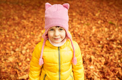 Happy little girl in autumn park. Autumn, childhood, nature and people concept - happy little girl over fallen leaves in park Stock Image