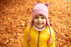Happy little girl in autumn park. Autumn, childhood, nature and people concept - happy little girl over fallen leaves in park Stock Photo