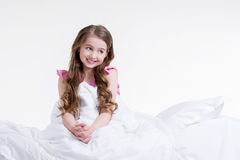 Happy little girl awake and sitting in the bed. Royalty Free Stock Image