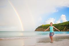 Happy little girl backgound the beautiful rainbow over the sea. Beautiful rainbow on caribbean beach. Happy little girl backgound the beautiful rainbow over the Royalty Free Stock Images