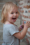 Happy little girl on the background of an old brick wall Royalty Free Stock Image