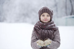 Happy little girl on the background of a winter park Stock Image