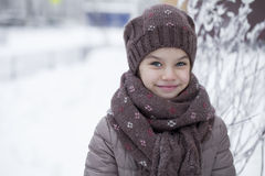 Happy little girl on the background of a winter park Stock Photos