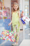 Happy little girl with bags in a large supermarket Royalty Free Stock Photo