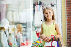 Happy little girl with bags in a large supermarket Stock Images