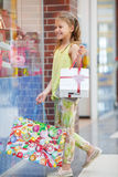 Happy little girl with bags in a large supermarket Royalty Free Stock Images