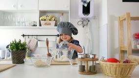 Happy little girl baker going to bake cookies in the kitchen. Close up stock video footage