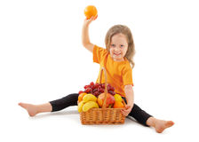 Happy little girl with basket of fruits Stock Photo
