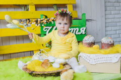 Happy little girl with a basket of small chickens sitting indoor Stock Images