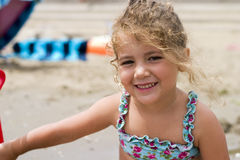 Happy little girl on the beach. Little girl playng happily on the beach Stock Image