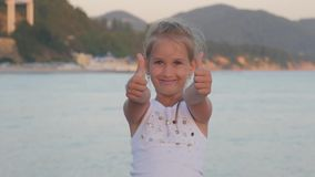 Happy little girl on the beach, little girl shows gesture super. Girl hand with thumb up perfect symbol is fine and the. Background of the sea stock video footage
