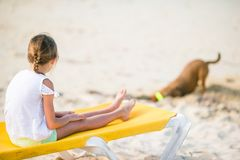 Happy little girl on the beach playing with dog. Cute little girl in hat at beach during caribbean vacation Stock Photography