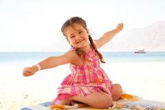 Happy little girl on the beach sitting on a lounger Stock Photos