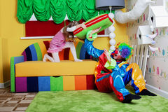 Happy little girl beats clown with a big pillow. Royalty Free Stock Image