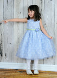 Happy little girl in beautiful blue dress pointing Stock Images