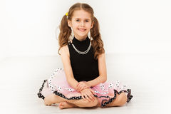 Happy little girl in beautiful dress and necklace. Portrait of happy little girl in beautiful dress and bead necklace, sitting on the floor against blanked royalty free stock photo