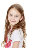 Happy little girl. Beautiful little girl with long brown hair to her waist . The girl smiles sweetly turning sideways to the camera. Close-up - Isolated on white royalty free stock image