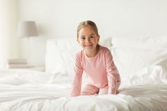 Happy little girl on bed at home bedroom. People, children and bedtime concept - happy little girl on bed at home bedroom Stock Photo