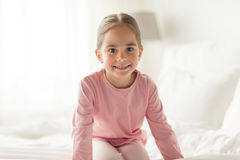 Happy little girl on bed at home bedroom. People, children and bedtime concept - happy little girl on bed at home bedroom Royalty Free Stock Image