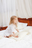 Happy little girl on a bed Stock Photography