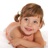 Happy little girl on the bedspread. A happy little girl is lying on the bedspread stock photos