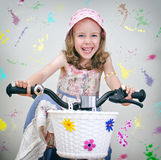 Happy little girl on a bicycle. Stock Images