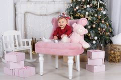 Little girl alone plays against a beautiful Christmas tree on Christmas Eve. A happy little girl with a big bow on her head, sits on a pink armchair with a big Stock Images