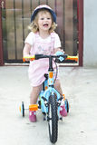 Happy little girl on bike Stock Image